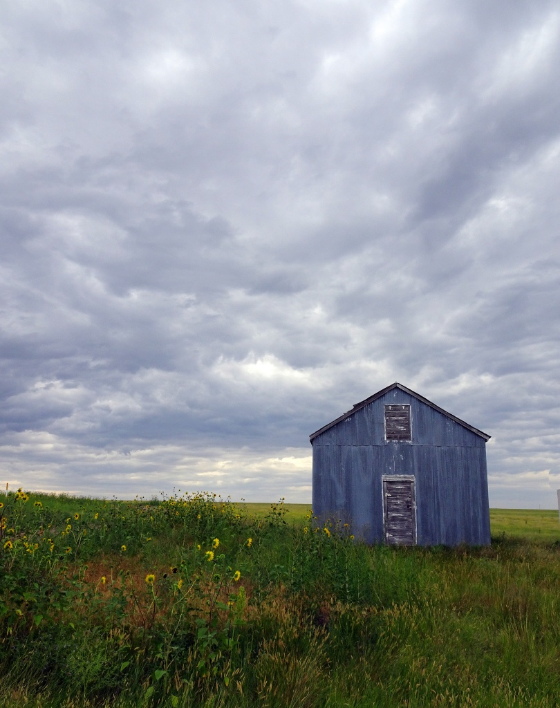 Abandoned barn on Colorado plains under cloudy sky