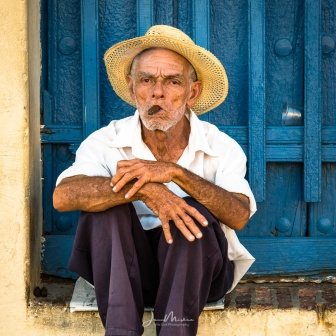 An older gentleman sits in a colorful Trinidad doorway smoking a cigar in his straw hat. Sony A7RIII 152mm 1/160@f11 ISO1600