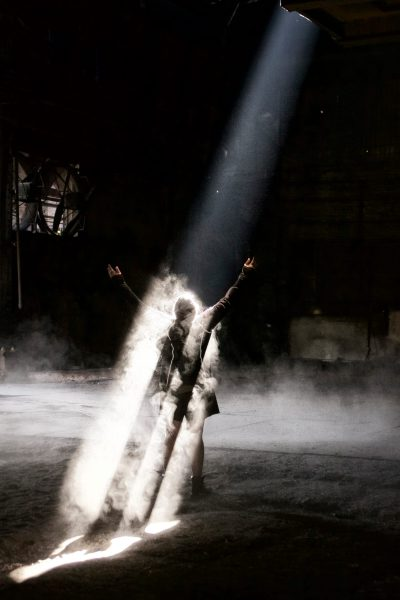 Person enveloped in dust in a beam of light abandoned building