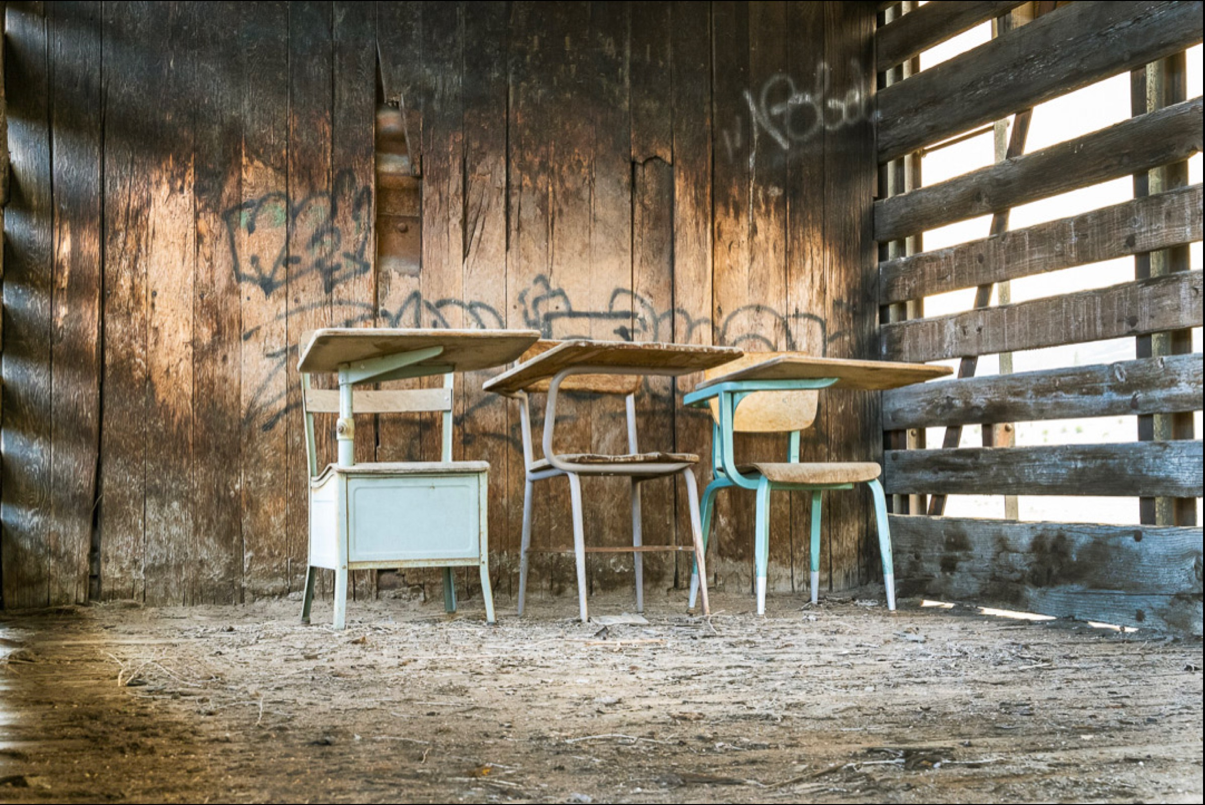 school desks weathered in abandoned train car